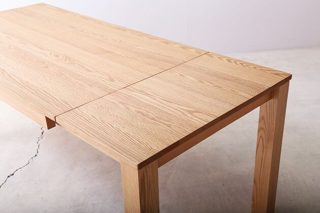 SE 伸長式無垢材ダイニングテーブル 天板に収納されたサブ天板を取り付けて伸長
